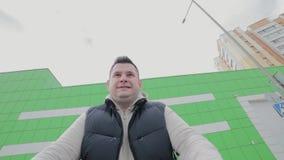 Человек имеет потеху на торговом центре автостоянки Счастливые смешные езды парня на магазинной тележкае Клиент с вагонеткой поку акции видеоматериалы
