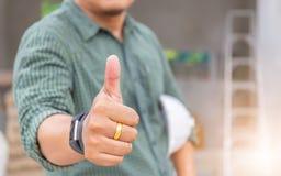 Человек инженера дела давая большой палец руки вверх как знак успеха над bl стоковые фотографии rf