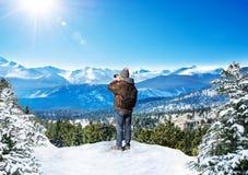 Человек используя камеру в горах на отключении зимы стоковое фото rf