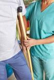 Человек используя костыли на физиотерапии стоковое фото