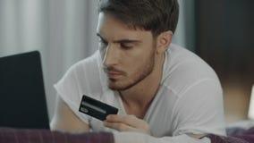 Человек используя кредитную карточку для онлайн-платежа на компьютере Приобретение технологии акции видеоматериалы