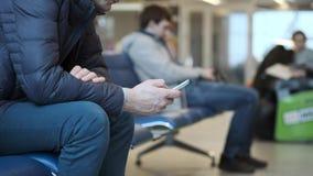 Человек используя мобильные телефоны на станции Использует smartphone на авиапорте Пишет сообщение SMS или печатает текст сток-видео