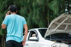 Человек используя мобильный телефон и вызывающ для помощи пока сломанный автомобиль стоковая фотография rf