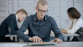 Человек используя ноутбук и планируя новый проект в его офисе видеоматериал