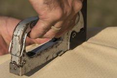 Человек используя сшиватель для того чтобы прикрепить материал крышки стоковые фото