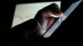 Человек используя телефон для онлайн торговой операции на обмене фондовой биржи сток-видео