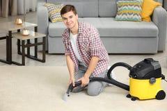 Человек используя уборщика пара пара в живущей комнате Стоковые Фото