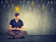 Человек используя умный телефон с яркой электрической лампочкой над головой Стоковые Изображения