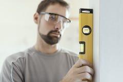 Человек используя уровень для того чтобы паять стену стоковое фото
