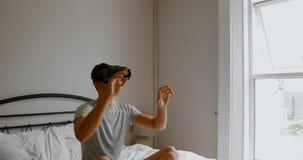 Человек используя шлемофон виртуальной реальности на кровати в спальне 4k сток-видео