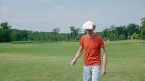 Человек используя шлемофон и игру VR виртуальной игры в парке акции видеоматериалы