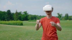 Человек используя шлемофон и приводы VR автомобиль в виртуальной игре в парке акции видеоматериалы