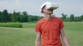 Человек используя шлемофон VR в беседах и усмехаться парка сток-видео