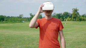 Человек используя шлемофон VR в парке и исправляет его видеоматериал