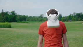 Человек используя шлемофон VR в парке и поворотах его голова вниз видеоматериал
