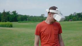 Человек используя шлемофон VR в парке и поворотах его голова вниз сток-видео