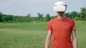 Человек используя шлемофон VR в парке и повороты к праву акции видеоматериалы