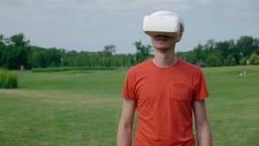 Человек используя шлемофон VR в парке и препонах увертывать акции видеоматериалы