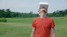 Человек используя шлемофон VR в парке и смотреть вокруг видеоматериал