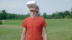 Человек используя шлемофон VR в парке и смотреть вокруг сток-видео