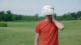 Человек используя шлемофон VR в парке и царапать его шею акции видеоматериалы