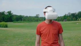 Человек используя шлемофон VR в парке видеоматериал