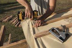 Человек используя электрическое scredriver для того чтобы прикрепить элементы конструкции стоковые изображения