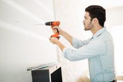 Человек используя электрическую дрель на стене Стоковое Изображение