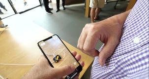 Человек испытывая новую характеристику ленты app AR в iPhone XS сток-видео