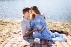 Человек и девушка ослабляя на реке побережья Стоковая Фотография RF
