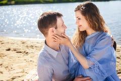 Человек и девушка отдыхая на реке побережья стоковое изображение