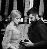 Человек и девушка с занятыми сторонами подсчитывают деньги в голубом бумажнике на предпосылке шкафа одежд Клиент с покупкой бород Стоковое Изображение RF