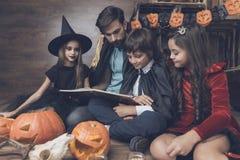 Человек и 3 дет в костюме извергов на хеллоуин сидят на окруженном поле и читают книгу Стоковая Фотография RF