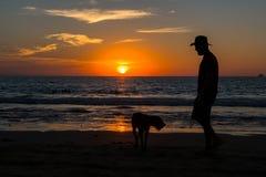 Человек и его прогулка собаки на заходе солнца стоковая фотография