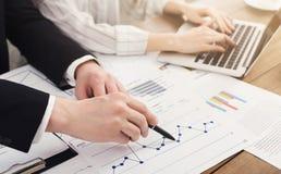 Человек и женщина анализируя финансовые диаграммы Стоковая Фотография RF
