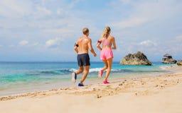 Человек и женщина бегут совместно на пляже Стоковая Фотография RF