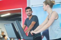 Человек и женщина бежать на третбане в спортзале Стоковые Фото
