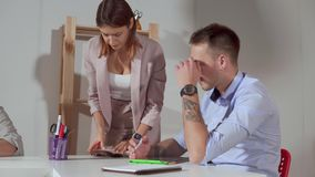 Человек и женщина бранят комната офиса, проверяя план работ сток-видео