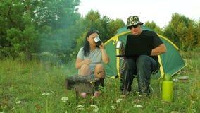 Человек и женщина варят мясо на гриле и выпивая чае Человек работает на компьтер-книжке акции видеоматериалы