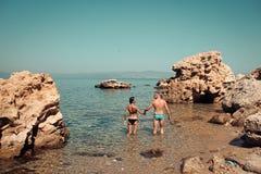 Человек и женщина в бикини стоят в море между рифом на солнечный день Пара в влюбленности стоит в воде около камня или утеса даль Стоковые Изображения