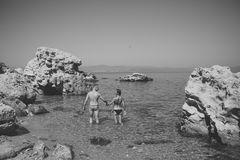 Человек и женщина в бикини стоят в море между рифом на солнечный день Пара в влюбленности стоит в воде около камня или утеса даль Стоковые Фото