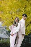 Человек и женщина в влюбленности стоят совместно под деревьями осени Стоковая Фотография