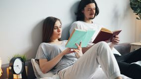 Человек и женщина в книгах чтения пижам в кровати дома поворачивая страницы акции видеоматериалы