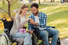 Человек и женщина в кресло-колясках встречали в парке Человек кладет кольцо на палец ` s женщины Стоковые Фото