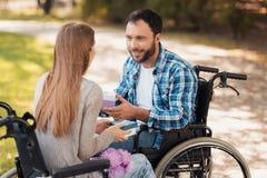 Человек и женщина в кресло-колясках встречали в парке Они обменивают подарки и улыбку на одине другого Стоковое Изображение RF