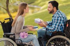 Человек и женщина в кресло-колясках встречали в парке Они обменивают подарки и улыбку на одине другого Стоковое Изображение