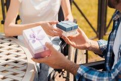 Человек и женщина в кресло-колясках встречали в парке Они обменивают подарки и улыбку на одине другого Стоковое Фото