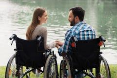 Человек и женщина в кресло-колясках сидят на береге озера Перед ими красивое озеро Они сидят рука об руку Стоковое Изображение RF