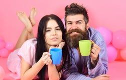 Человек и женщина в отечественных одеждах, пижамах Человек и женщина на усмехаясь положении сторон, розовой предпосылке Пары в пи Стоковое Фото