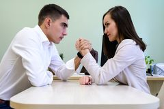 Человек и женщина в офисе одевают бороться на его руках над столом в офисе Стоковые Изображения